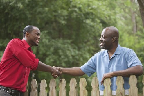 african-american-neighbors-greeting-each-other-over-fence-137924297-5a9863920e23d900370c683e