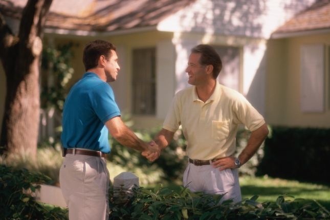 Two men shaking hands over fence